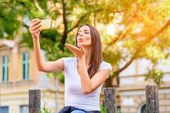 Une femme en parc prenant un Selfie avec son Smartphone Images stock