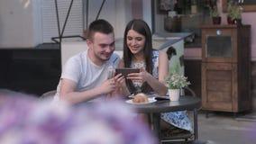 Une femme en photos de observation d'un homme sur un smartphone un café d'été clips vidéos