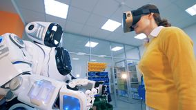 Une femme en verres augmentés de réalité met ses paumes sur les paumes d'un cyborg banque de vidéos