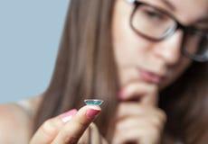 Une femme en verres tient un verre de contact bleu sur son doigt photographie stock
