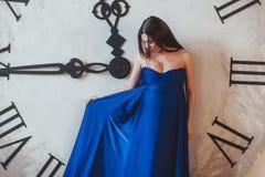 Une femme enceinte dans une belle longue robe bleue se tenant devant l'horloge énorme Photos stock