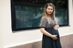 Une femme enceinte dans une robe rayée noire et blanche avec de longs cheveux blonds images stock