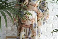 Une femme enceinte dans une robe tenant ses mains sur son estomac Concept de grossesse, de maternité, de préparation et d'attente Photo stock