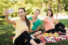 Une femme enceinte dans un T-shirt jaune s'assied avec ses amies enceintes sur un pique-nique en parc et fait un selfie Photographie stock