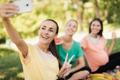 Une femme enceinte dans un T-shirt jaune s'assied avec ses amies enceintes sur un pique-nique en parc et fait un selfie Image libre de droits