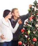 Une femme enceinte et un homme célébrant Noël Image stock