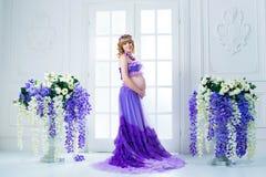Une femme enceinte heureuse dans une longue jupe pourpre pose dans le studio sur un fond des fleurs Photographie stock