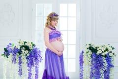 Une femme enceinte heureuse dans une longue jupe pourpre pose dans le studio sur un fond des fleurs Image libre de droits