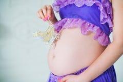 Une femme enceinte heureuse dans une longue jupe pourpre pose dans le studio sur un fond des fleurs Images libres de droits