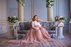 Une femme enceinte s'asseyant dans une belle robe sur le divan Le concept de la maternité Photographie stock libre de droits