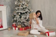 Une femme enceinte s'asseyant par l'arbre de Noël ouvre des cadeaux de Noël images libres de droits