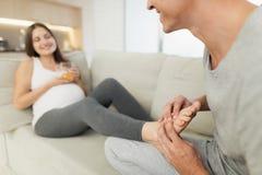 Une femme enceinte se trouve sur un sofa léger Un homme s'assied à côté de elle et malaxe ses pieds Photo libre de droits