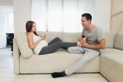 Une femme enceinte se trouve sur un sofa léger Un homme s'assied à côté de elle et malaxe ses pieds Photo stock