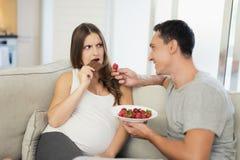 Une femme enceinte se trouve sur un sofa léger Un homme s'assied à côté de elle Ils mangent des fraises et des bonbons Photos stock