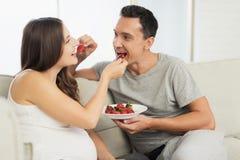 Une femme enceinte se trouve sur un sofa léger Un homme s'assied à côté de elle Ils mangent des fraises et des bonbons Images stock