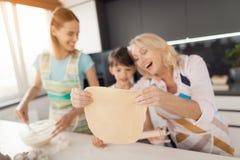 Une femme enseigne son fils à faire cuire les biscuits faits maison La grand-mère les aide Ils ont roulé la pâte dans un grand ce Images stock