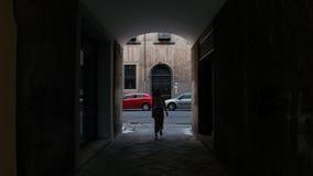 Une femme entre dans une allée foncée et avance banque de vidéos