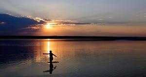 Une femme entre dans l'eau sur le fond du coucher du soleil Images stock