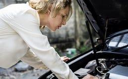 Une femme essayant de fixer la voiture photos libres de droits