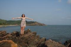 Une femme est heureuse au sujet du début des vacances Une femme se tient sur une roche avec ses bras tendus au vent photos libres de droits