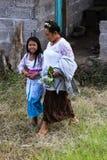 Une femme et des fleurs de transport d'une fille quittent leur maison dans la robe cérémonieuse sur le chemin à un festival relig image libre de droits