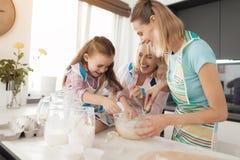 Une femme et sa mère enseignent leur fille à faire cuire les gâteaux faits maison Les trois d'entre eux malaxent la pâte Photo libre de droits
