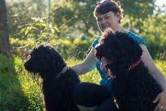Une femme et ses deux terriers russes noirs sont sur une promenade en parc Image stock