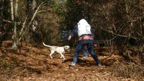 Une femme et un enfant jouent avec un chien dans la forêt banque de vidéos