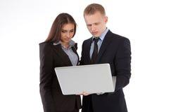 Une femme et un homme d'affaires travaillant ensemble sur un ordinateur portable Photo stock