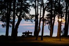 Une femme et un homme s'asseyant sur un banc et rencontrant le coucher du soleil sur la plage photo stock