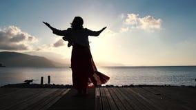 Une femme faisant des exercices d'entonnoir, tournant près de la mer au lever du soleil au ralenti banque de vidéos