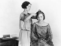 Une femme faisant les cheveux d'une autre femme (toutes les personnes représentées ne sont pas plus long vivantes et aucun domain Images stock
