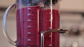 Une femme fait un smoothie de fruit dans un mélangeur clips vidéos
