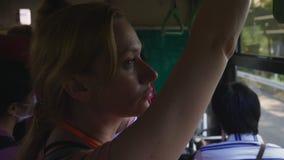Une femme fatiguée monte sur un autobus tout en se tenant et se tenant sur un rail banque de vidéos