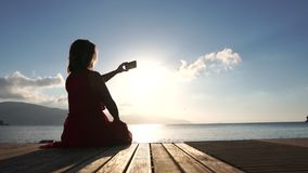 Une femme filme le paysage marin sur son smartphone au lever du soleil, au ralenti banque de vidéos