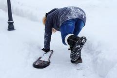 Une femme a glissé et est tombée sur la route d'hiver Image libre de droits