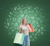 Une femme heureuse avec les paniers colorés des boutiques de fantaisie Des icônes d'achats sont dessinées sur le mur vert Image stock