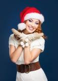 Une femme heureuse en hiver vêtx sur la BG bleue Photos stock