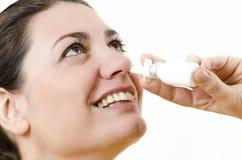 Une femme heureuse à l'aide de la pulvérisation nasale Images libres de droits