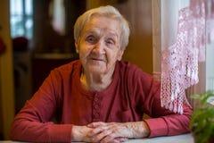 Une femme heureuse pluse âgé s'asseyant à la table dans la maison Image stock