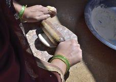Une femme indienne rurale préparant le chapati images libres de droits