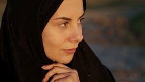 Une femme islamique dans un hijab regarde dans la caméra banque de vidéos