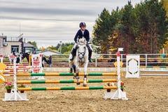 Une femme jockey de jeune femme sur un cheval exécute un saut à travers la barrière photo stock