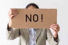 Une femme juge une bannière avec l'inscription AUCUNE images stock