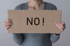 Une femme juge une bannière avec l'inscription AUCUNE photo stock