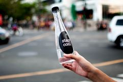 Une femme juge une bouteille platic avec de l'eau extérieure Image stock