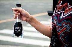 Une femme juge une bouteille platic avec de l'eau extérieure Photographie stock libre de droits