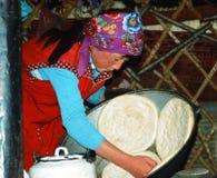 Une femme kirghiz fait le pain cuire au four dans un yurta Photographie stock libre de droits