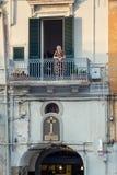 Une femme locale plus âgée regardant à la rue du balcon dans Polignano une jument, Italie image libre de droits