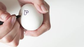 Une femme méconnaissable tenant un marqueur dessine des coeurs dans le noir sur un oeuf cassé pour les vacances de Pâques Pour le banque de vidéos